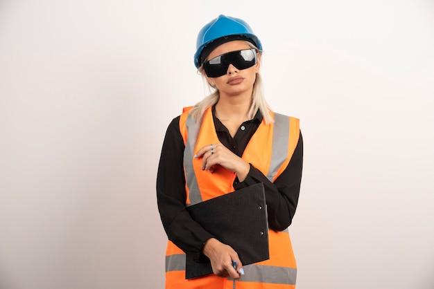 Vrouwelijke ingenieur in glazen die zich voordeed op witte achtergrond. hoge kwaliteit foto