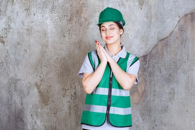 Vrouwelijke ingenieur in groen uniform en helm die dankbaarheid voelt.