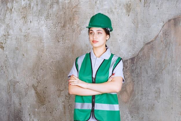 Vrouwelijke ingenieur in groen uniform en helm die de armen kruist en ziet er professioneel uit.