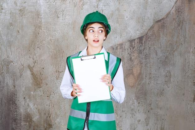 Vrouwelijke ingenieur in groen uniform en helm die de projectlijst demonstreert en ziet er gestrest en doodsbang uit.