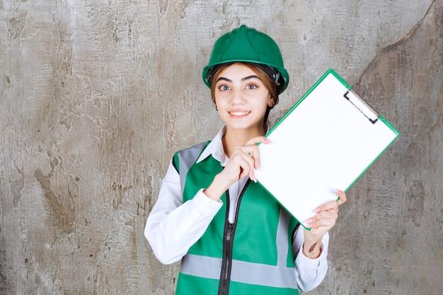 Vrouwelijke ingenieur in groen uniform en helm die de projectlijst demonstreert.