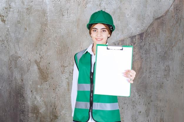 Vrouwelijke ingenieur in groen uniform en helm die de projectlijst demonstreert