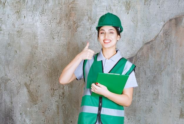 Vrouwelijke ingenieur in groen uniform en helm die de projectmap vasthoudt en een positief handteken toont
