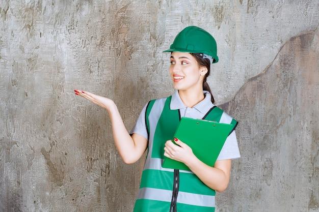 Vrouwelijke ingenieur in groen uniform en helm die de projectmap vasthoudt en naar iemand wijst.