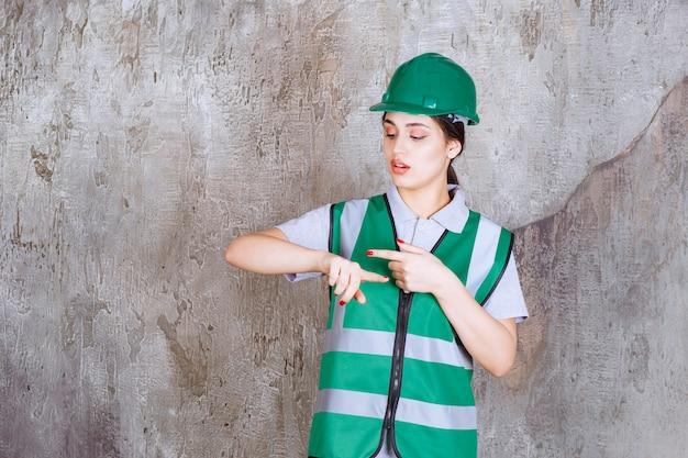 Vrouwelijke ingenieur in groen uniform en helm die de tijd laat zien.