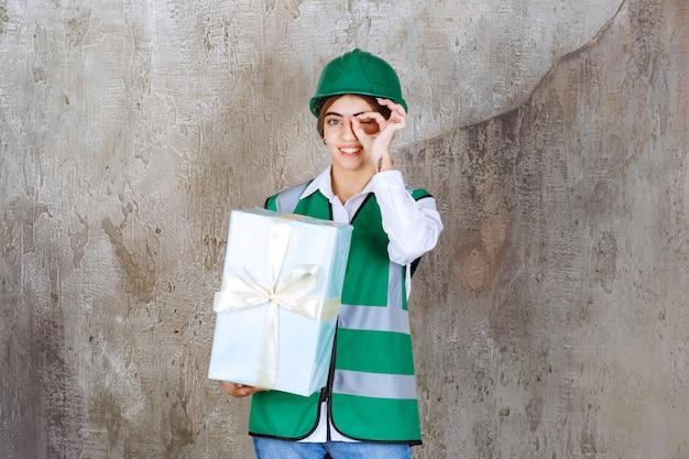 Vrouwelijke ingenieur in groen uniform en helm die een blauwe geschenkdoos vasthoudt en een teken van plezier toont.