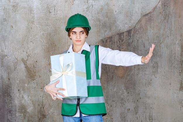 Vrouwelijke ingenieur in groen uniform en helm die een blauwe geschenkdoos vasthoudt en iets weigert.
