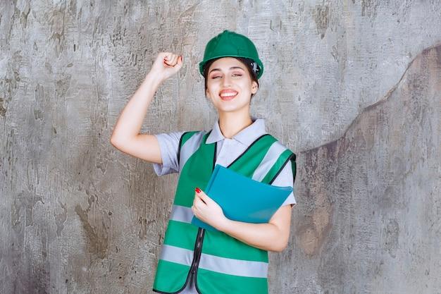 Vrouwelijke ingenieur in groen uniform en helm die een blauwe projectmap houdt en positief handteken toont.