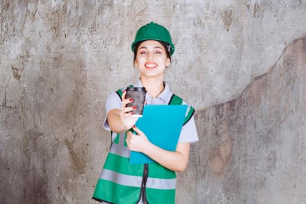 Vrouwelijke ingenieur in groen uniform en helm die een blauwe projectmap vasthoudt en een koffiekopje aanbiedt aan haar collega