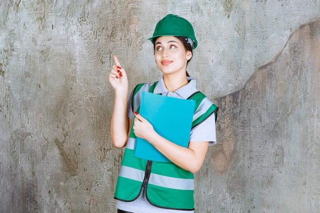 Vrouwelijke ingenieur in groen uniform en helm die een blauwe projectmap vasthoudt en naar het gebouw wijst.