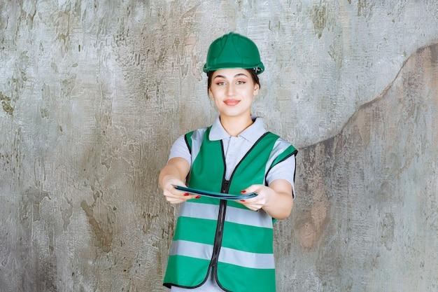 Vrouwelijke ingenieur in groen uniform en helm die een blauwe projectmap vasthoudt en ter verificatie aanbiedt.