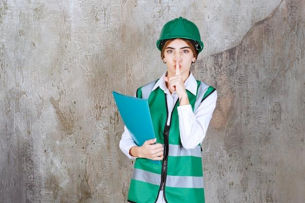 Vrouwelijke ingenieur in groen uniform en helm die een groene projectmap houdt en om stilte vraagt.