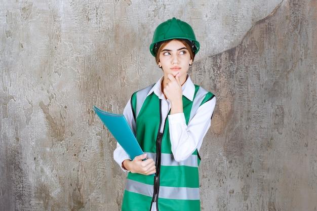 Vrouwelijke ingenieur in groen uniform en helm die een groene projectmap vasthoudt, denkt en analyseert