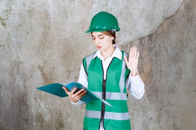 Vrouwelijke ingenieur in groen uniform en helm die een groene projectmap vasthoudt, deze leest en opmerkingen maakt.