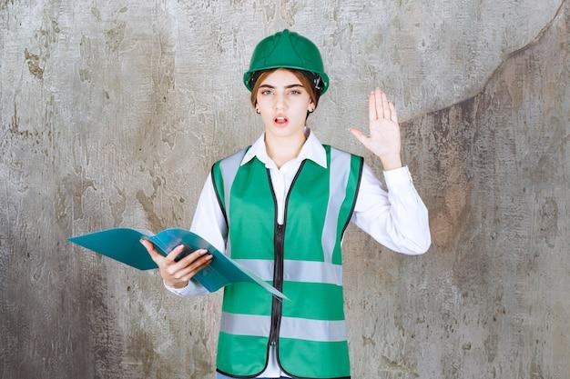 Vrouwelijke ingenieur in groen uniform en helm die een groene projectmap vasthoudt, deze leest en opmerkingen maakt
