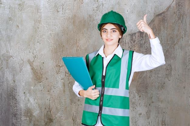 Vrouwelijke ingenieur in groen uniform en helm die een groene projectmap vasthoudt en een positief handteken toont.