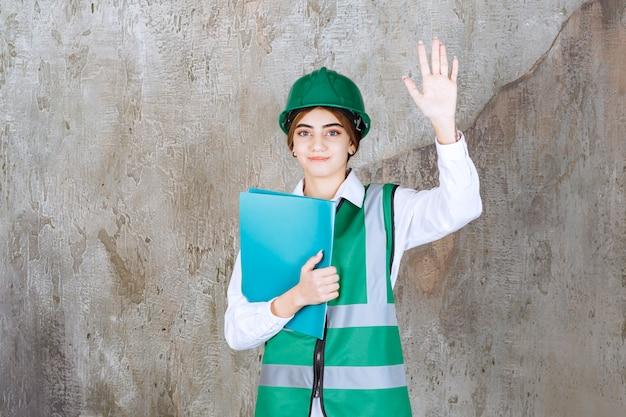 Vrouwelijke ingenieur in groen uniform en helm die een groene projectmap vasthoudt en iemand begroet.