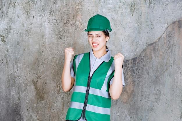 Vrouwelijke ingenieur in groen uniform en helm die haar vuisten laat zien en zich positief voelt