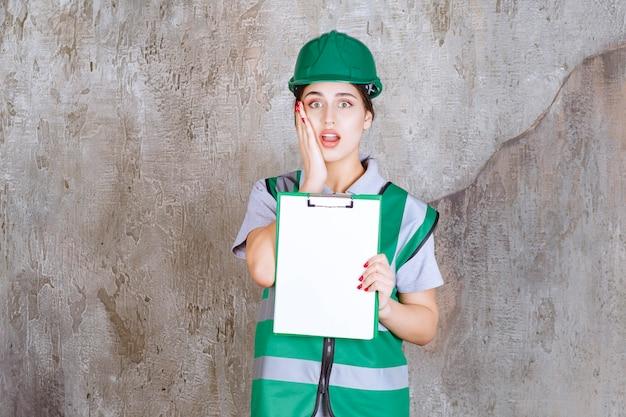 Vrouwelijke ingenieur in groen uniform en helm die het projectblad demonstreert en ziet er doodsbang en bang uit.
