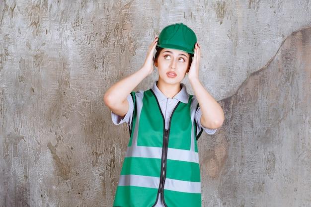 Vrouwelijke ingenieur in groen uniform en helm die hoofd vasthoudt en ziet er doodsbang uit