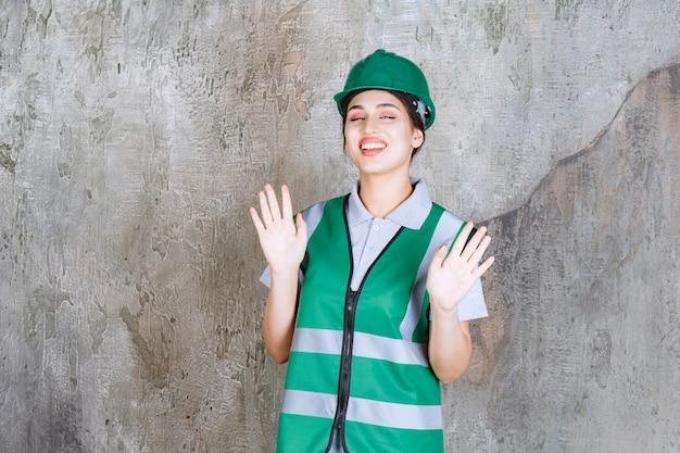 Vrouwelijke ingenieur in groen uniform en helm die iets tegenhoudt.