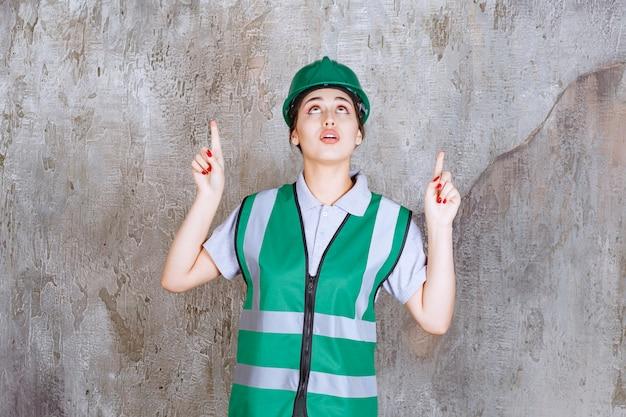 Vrouwelijke ingenieur in groen uniform en helm die naar boven wijst met emoties.