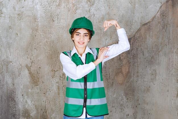 Vrouwelijke ingenieur in groen uniform en helm die op betonnen muur staat en haar armspieren demonstreert.