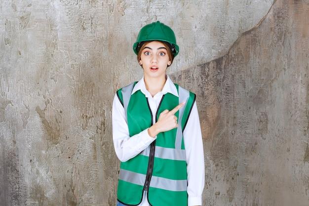 Vrouwelijke ingenieur in groen uniform en helm die op de betonnen muur staat en de rechterkant laat zien.