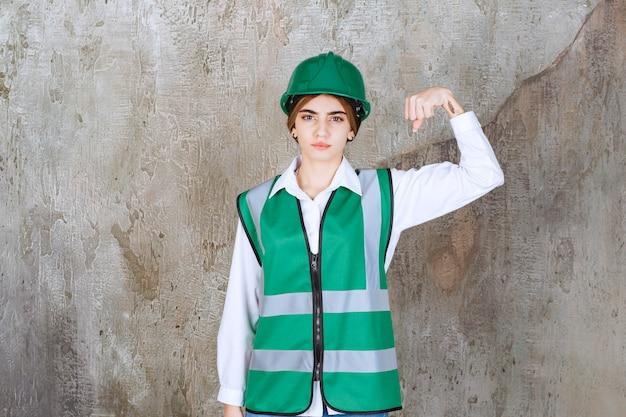 Vrouwelijke ingenieur in groen uniform en helm die op een betonnen muur staat en haar armspieren demonstreert