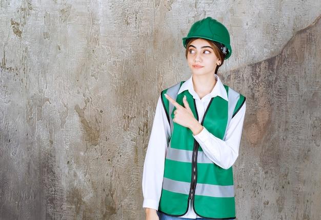 Vrouwelijke ingenieur in groen uniform en helm die op een betonnen muur staat en naar de linkerkant wijst