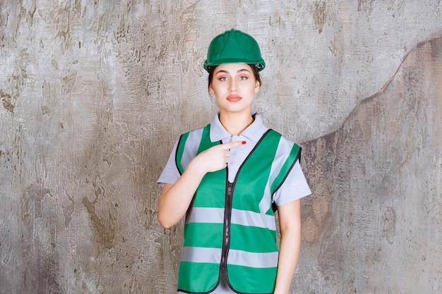 Vrouwelijke ingenieur in groen uniform en helm die rechterkant toont.
