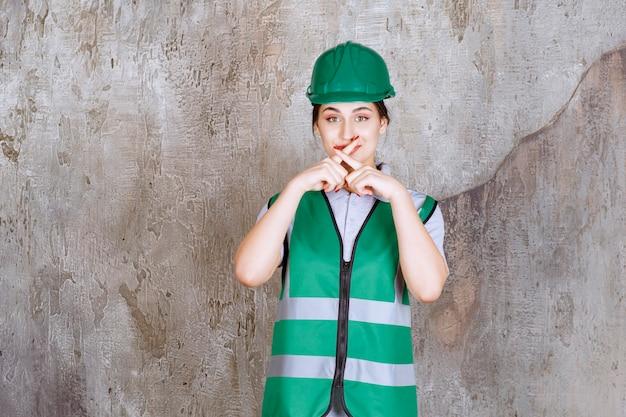 Vrouwelijke ingenieur in groen uniform en helm die vraagt om niets te zeggen