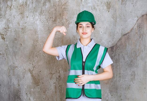 Vrouwelijke ingenieur in groen uniform en helm haar armspieren demonstreren.