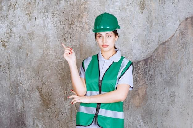 Vrouwelijke ingenieur in groen uniform en helm links met emoties tonen.