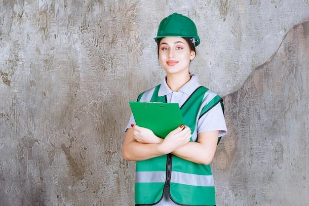 Vrouwelijke ingenieur in groen uniform en helm met de projectmap.