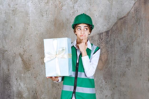 Vrouwelijke ingenieur in groen uniform en helm met een blauwe geschenkdoos en kijkt verward en doodsbang
