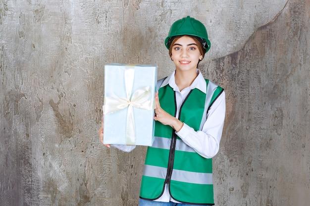 Vrouwelijke ingenieur in groen uniform en helm met een blauwe geschenkdoos.