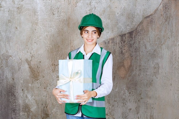 Vrouwelijke ingenieur in groen uniform en helm met een blauwe geschenkdoos
