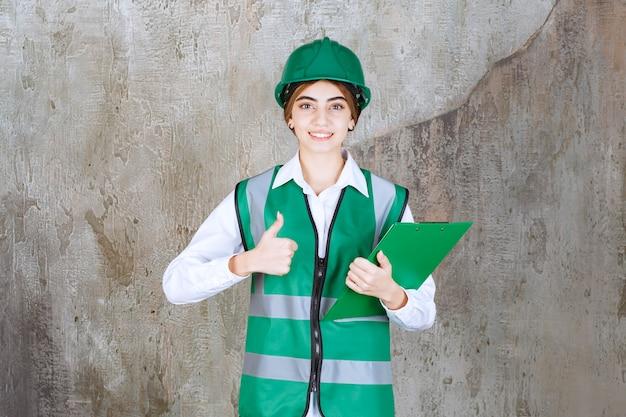 Vrouwelijke ingenieur in groen uniform en helm met een groene projectmap en duim omhoog.