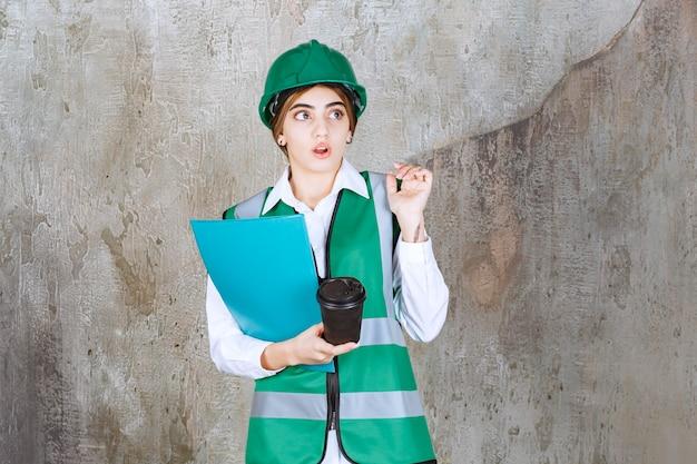 Vrouwelijke ingenieur in groen uniform en helm met een groene projectmap en een kopje drank en ziet er verward en opgewonden uit.