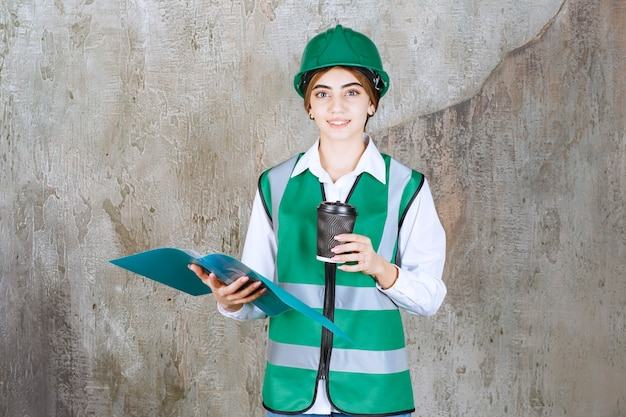 Vrouwelijke ingenieur in groen uniform en helm met een groene projectmap en een kopje drank