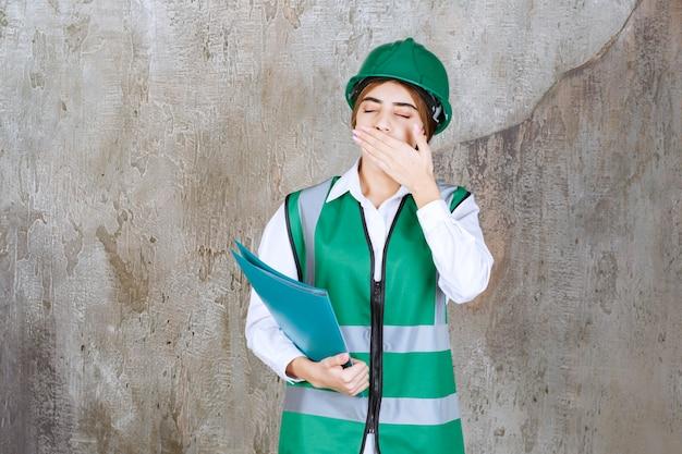 Vrouwelijke ingenieur in groen uniform en helm met een groene projectmap en ziet er moe en slaperig uit.