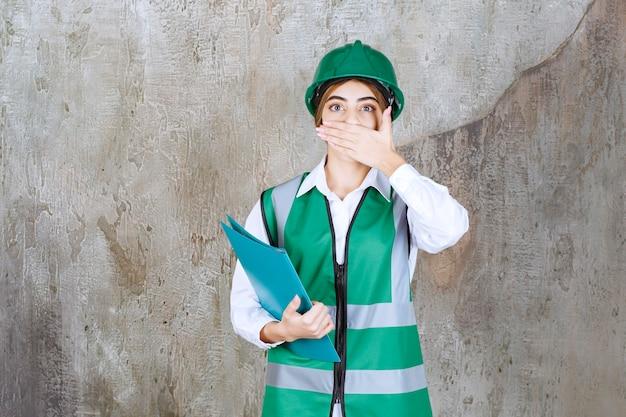 Vrouwelijke ingenieur in groen uniform en helm met een groene projectmap en ziet er moe en slaperig uit
