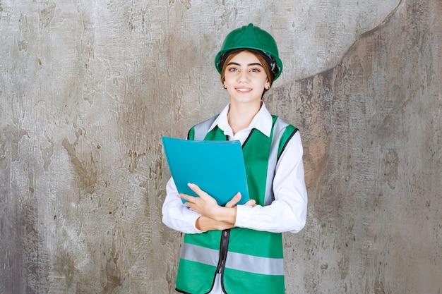 Vrouwelijke ingenieur in groen uniform en helm met een groene projectmap.