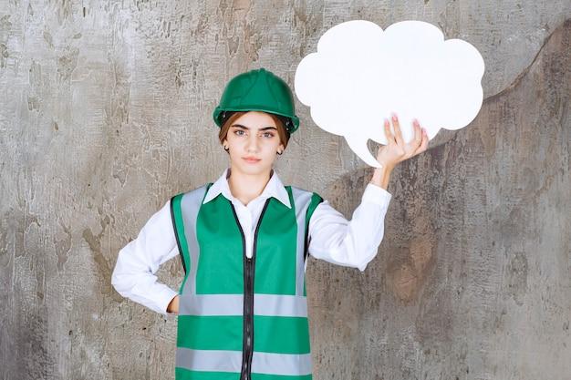 Vrouwelijke ingenieur in groen uniform en helm met een infobord in de vorm van een wolk.