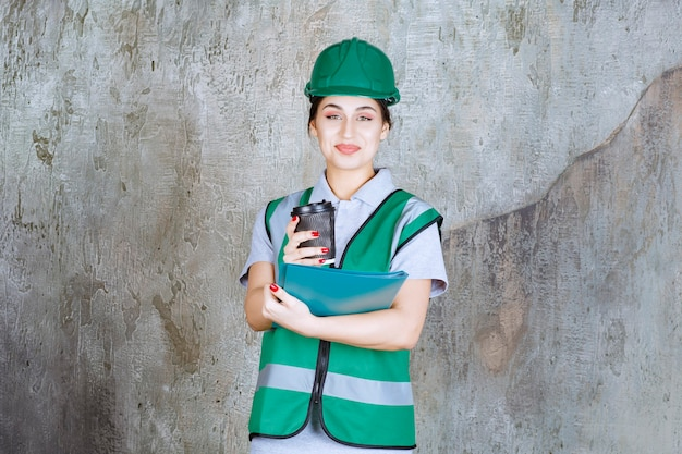 Vrouwelijke ingenieur in groen uniform en helm met een zwarte koffiekop en een blauwe projectmap.