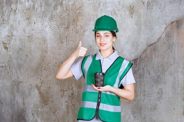 Vrouwelijke ingenieur in groen uniform en helm met een zwarte koffiekop en genietend van het product