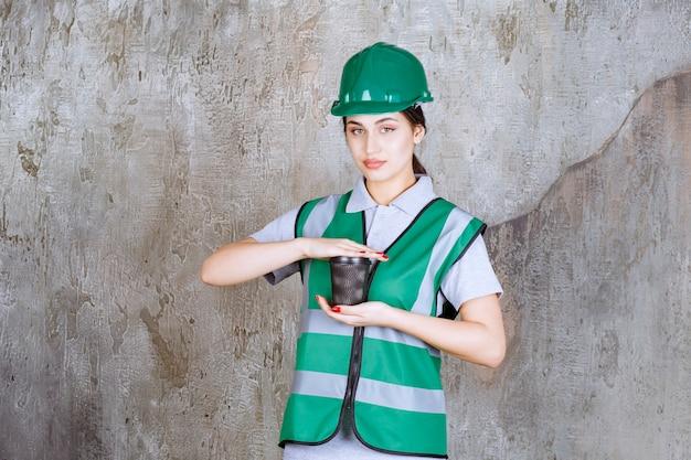 Vrouwelijke ingenieur in groen uniform en helm met een zwarte koffiekop.