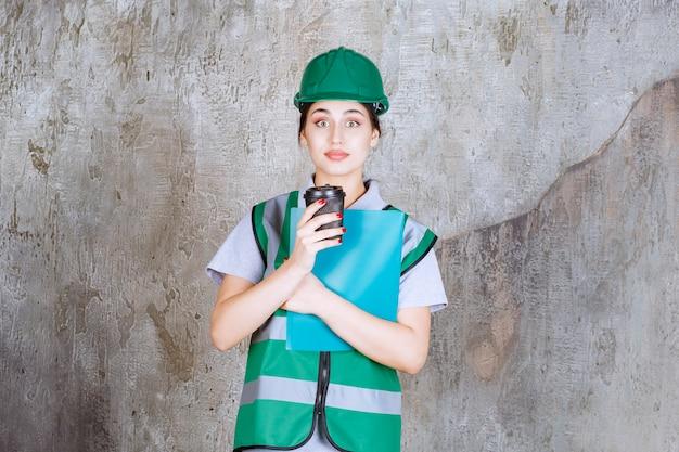 Vrouwelijke ingenieur in groen uniform en helm met een zwarte koffiekopje en een blauwe projectmap.