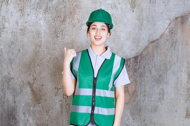 Vrouwelijke ingenieur in groen uniform en helm met iets erachter.